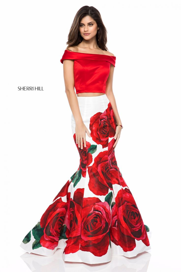 This Sherri Hill 51850 red print long party dress features a solid crop top with a foldover off-the-shoulder neckline, paired with a floral mermaid skirt. The bow-appliqued cutout back offsets the court train in this two piece prom gown.