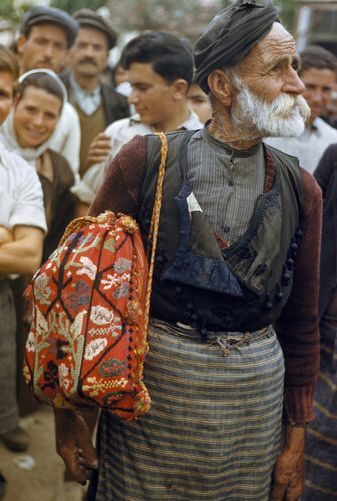 An elderly farmer carries a brightly colored sack. Moires-Crete. National Geographic's Greece in Color from the 1920s Photographer: Maynard Owen Williams in the 1920s