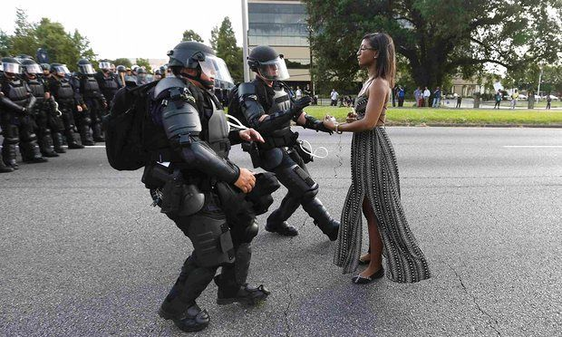 Continuing with my different people, different places, different jobs. different lives series. This photo shows Iesha L Evans standing still in the face of two Louisiana state troopers in riot gear. I am posting it here to refocus our attention away from other horrible things, to the power that one person can have to help change perceptions and realities. Now if you focus on the picture, I like to think that the image of her erect strong body is mirrored in that very old tree in back of her.