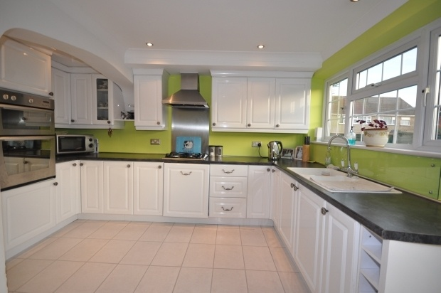 Lime green kitchen with white painted cabinets.