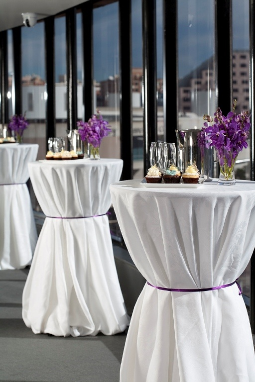 cocktail tables with white linens and purple ribbon...would probably prefer black ribbon though