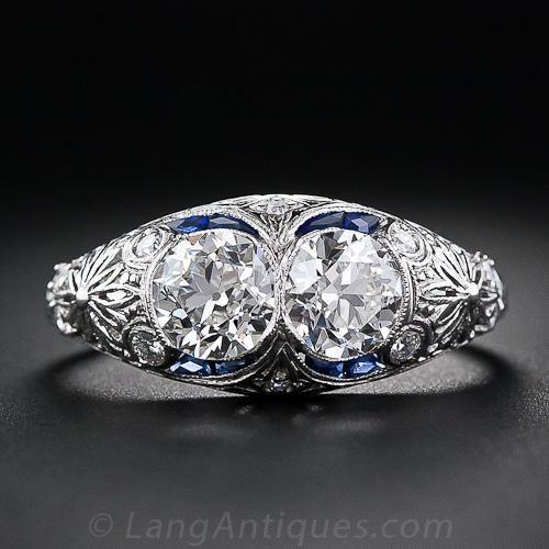 Dos son mejor que uno! Un par de faros de diamantes con sus brillos encendido está acentuado con mechones delgados de zafiros calibre de corte en el ring extraordinaria original de Art Deco de doble piedra de diamante, magistralmente elaborado en platino - alrededor de 1930. El peso total de los dos de alto calibre de edad diamantes de remoción de corte es 1,66 quilates. De una belleza única. Tamaño del anillo 8 3/4.