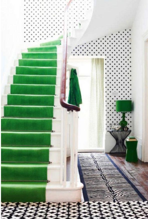 Het zwart-wit patroon op de vloer combineert fraai met het contrasterende groen op de trap en lamp.