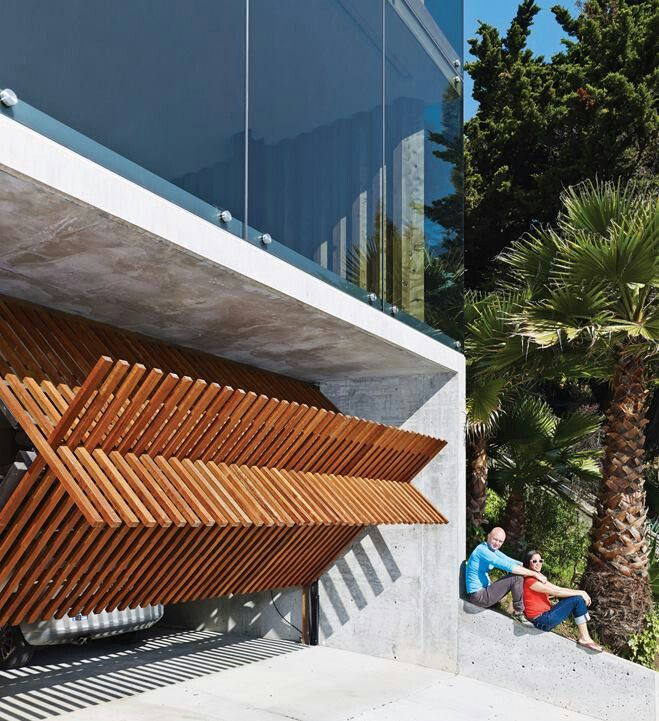 Porta basculante em barras de madeira com efeito interessante na abertura.
