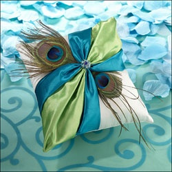 White wedding ring pillow finished with blue and green sash and peacock feathers