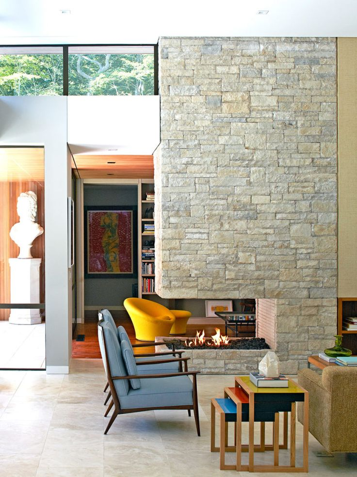 The stone clad fireplace wall divides the living room into two parts