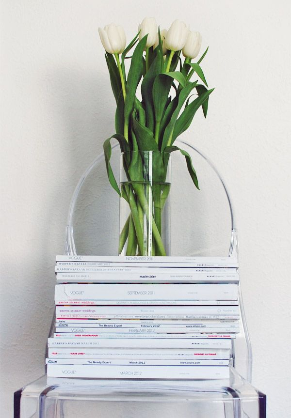 The famous ghost chair stacked with magazines and used to display glass vase filled with white tulips and their wonderfully green stems. It's a magnificent vignette. Visual happiness.Biddy Craft: