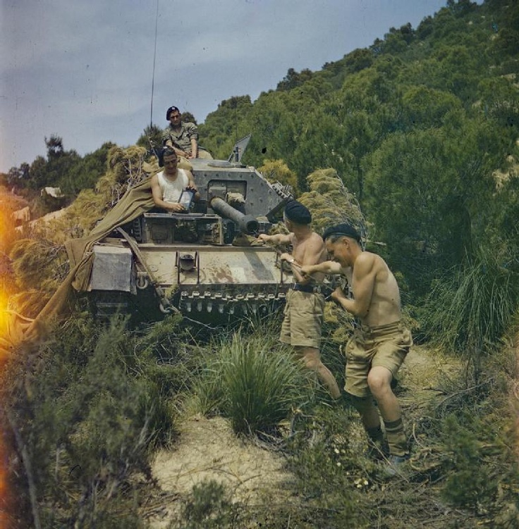 THE BRITISH ARMY IN NORTH AFRICA, 1943: THE DRIVE ON TUNIS. Sergeant Elms of 16/5 Lancers and his tank crew at El Aroussa; Trooper Bates, Royal Armoured Corps, Signalman Bower, Royal Corps of Signals, and Trooper Goddard, Royal Armoured Corps, clean the 6-pounder gun of their Crusader tank while preparing for the drive on Tunis.