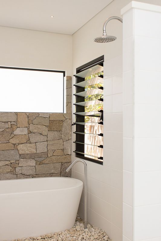 bathroom detail with stone wall and freestanding bath (SD Interiors)