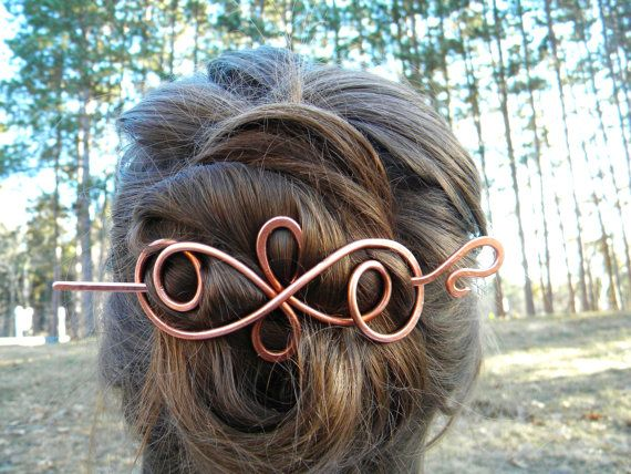 Beautiful handcrafted hair slide. Slide mimics a flowing ribbon. Hair shown braided on top and finished twisted into a bun.