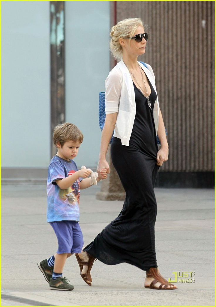 Gwyneth Paltrow - black dress, white short sleeve cardigan, feather necklace, zip up sandals and cool glasses.