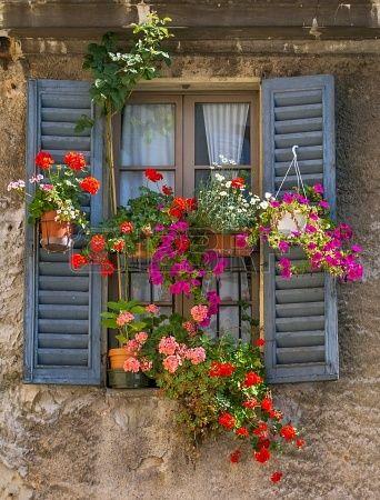 Vintage ventana con contraventanas de madera abiertas y flores frescas