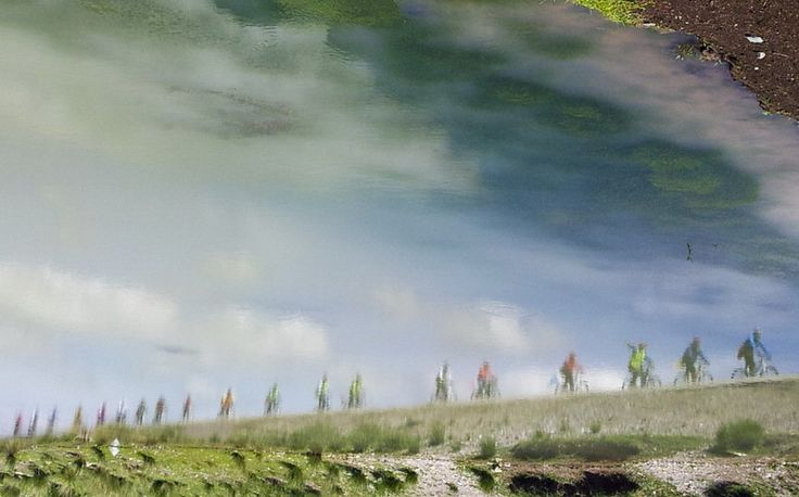 Riding friends set off beautiful shadow in the water Cycling around the Qinghai Lake of China
