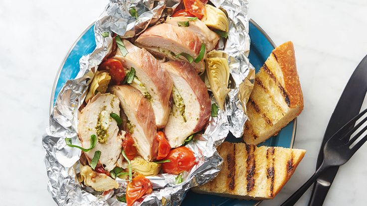 If you only make one foil-pack meal in your life, let it be this one! Pesto- and fresh mozzarella-stuffed chicken gets wrapped in prosciutto and nestled among Italian vegetables swimming in a divine sauce that's perfect for soaking up with crusty grilled bread — if there's any left!