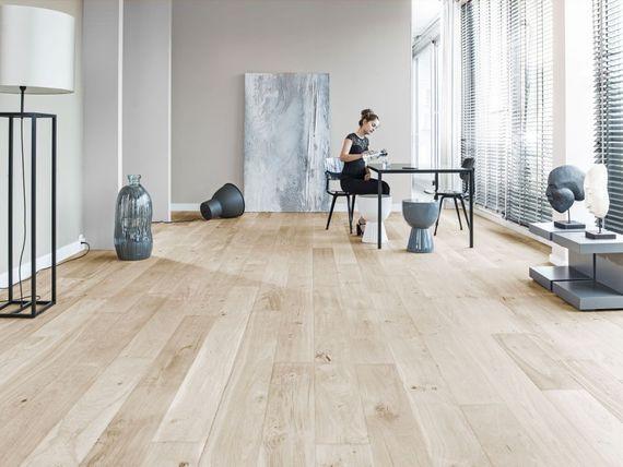 Eine Frau Sitzt In Einem Modernen Raum Mit Parkettboden Parkettboden Parkett Boden