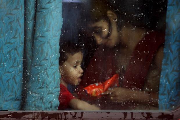 Sorella acqua - India, Nuova Dehli, una donna e il suo bambino incorniciati dal finestrino di un treno.