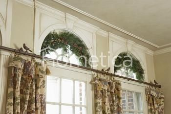 WINDOW TREATMENTS: Palladian windows above pastoral printed curtains, small birds are sitting on the curtain rod, Christmas greenery swags in arches