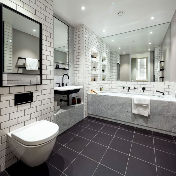 A Period Property That Perfectly Combines Classic and Contemporary Decor. Carrera marble casing around the bath and basin enhances the en suite's luxurious feel. Bathroom by Amos and Amos, Credit: Grant Silverman. amos and amos bathroom classical carrera marble luxurious en suite tiling mirrored metro tiles black grouting monochrome black and white bathtub tub