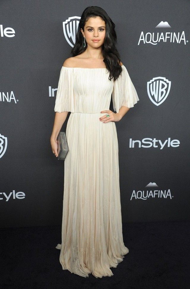 Selena Gomez wears a J. Mendel blush hand-pleated off-the-shoulder gown with Jacob & Co. jewelry and a metallic Rauwolf clutch.