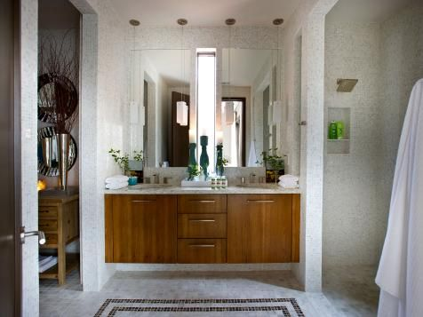 The sleek, wood vanity stands out in this neutral, contemporary master bathroom from the HGTV Green Home 2012. Tiled from the walls to the floor in a sea of crisp white, mosaic tile in emperador dark marble and brown glass adds some color and echoes the design of decorative roofline dovecotes. An open shower creates a spacious and airy feel.