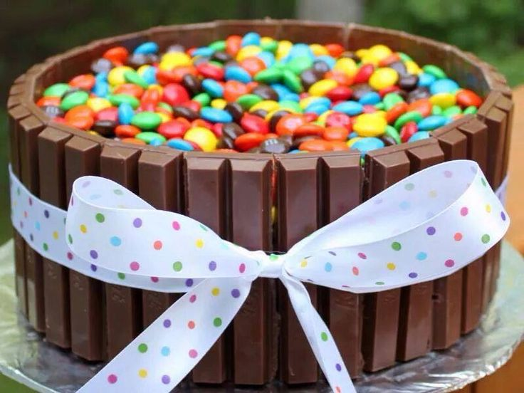 Chocolate cake topped with m&ms and surrounded by Kit-Kat bars