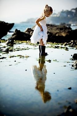 Little Girl wearing white dress with gumboots - reflection in water