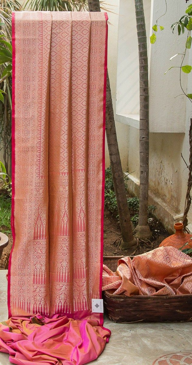 EXQUISITE PINK IRIDESCENT YELLOW BENARES SILK HAS INTRICATELY WOVEN FLORAL BHUTAS IN GOLD ZARI ALL OVER. THE PINK SHOT YELLOW WITH GOLD ZARI FLORAL DESIGN BORDER AND PALLU GIVES THE SAREE GRAND LOO...