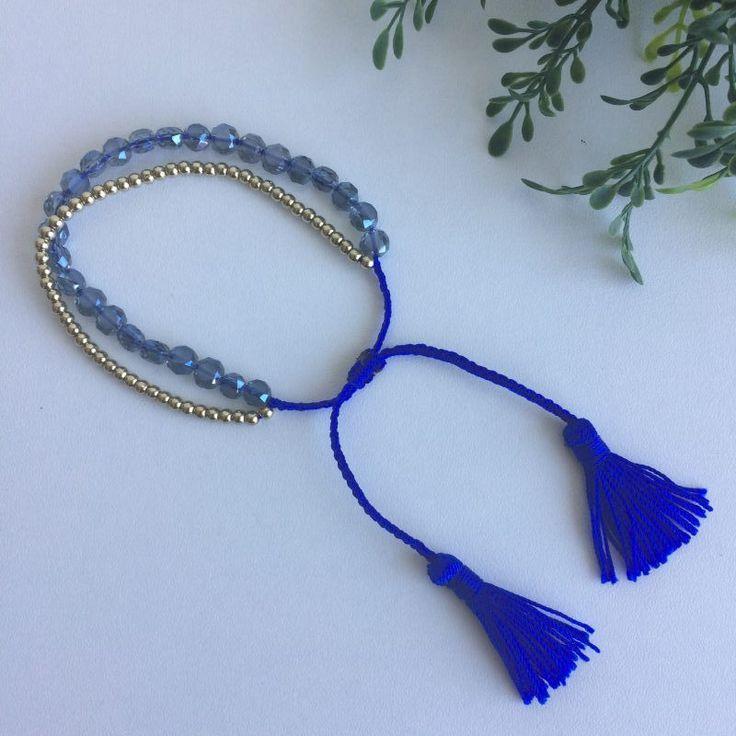 blauw armbandje met tassel - 4leafs4joy - lovely - blauw -blinkend en vlak - goud - klein en rond - stel af doormiddel van een knoopje - twee tassels