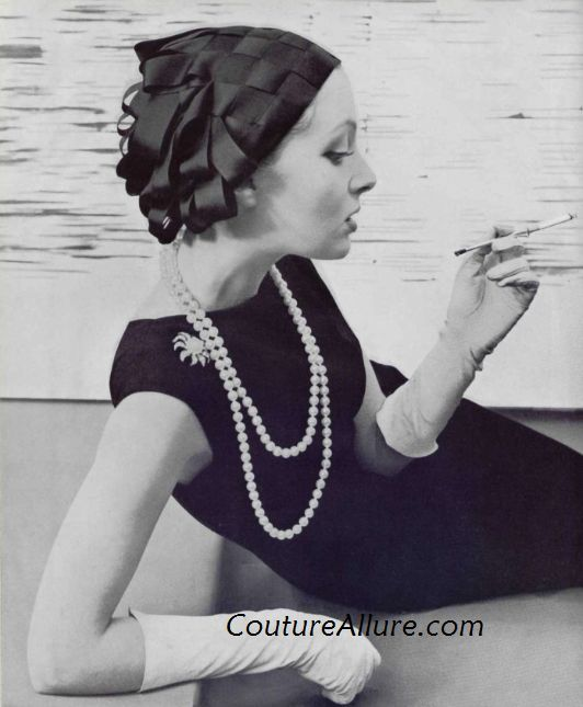 Jacques Fath weaves black silk ribbons into a tight fitting cap, 1957
