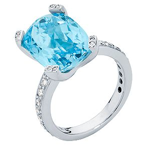 A stunning cushion cut Topaz with a diamond encrusted band makes for a show-stopping dress ring