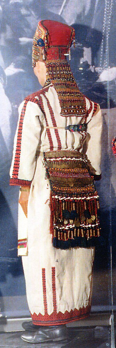 The back aprob was originally part of the dress of a married woman, but later was worn by unmarried girls as well. The upper part was embroidered by the woman herself, but the lower portion was made by specialists, and included tassels, fringe, chains, cowries, coins and beads. It was said of Erzya women that you heard them coming long before you saw them.