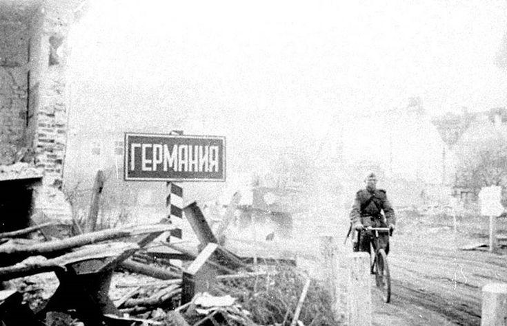 """Пограничный столб с надписью """"Германия"""" (на русском языке) на улице разрушенного в ходе боев немецкого города. 1945 г. Восточная Пруссия."""