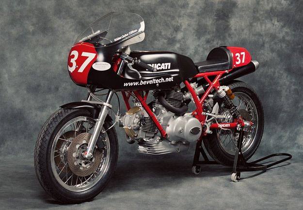 """In Australia, Tony Hannagan of BevelTech is the man to call if you need help with a classic Ducati. And this sleek black-and-red beauty is his latest build. 'Vern R' is a Ducati 900SS-based racer designed for the BEARS series—meaning """"British, European, American Racing and Supporters"""", a club set up by the late, great John Britten. Hannagan has taken the frame and motor from one of his heavily modified road bikes, and developed the machine for the track using the time-honoured principle of…"""