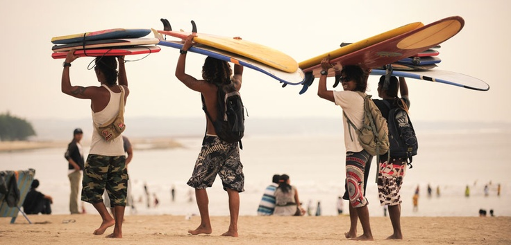 Surf's Up! Excitement begins with laughter and smiles as these beach boys cheerfully carry their surfboards on their head.
