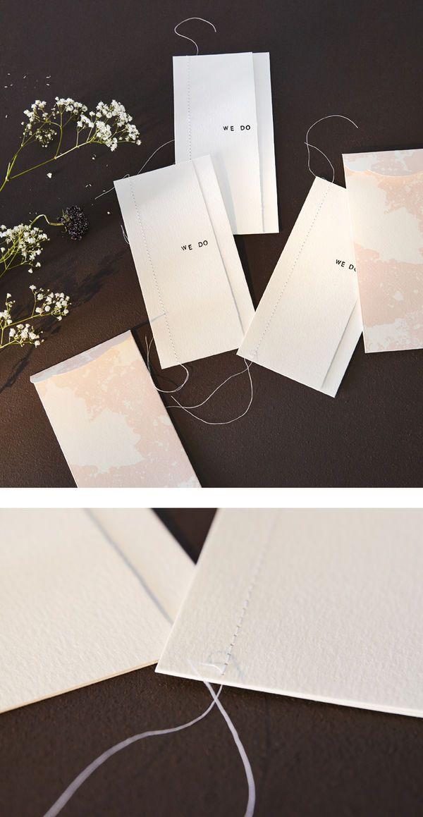 Hvite bryllupsinvitasjonskort får et personlig preg med stempler og søm.