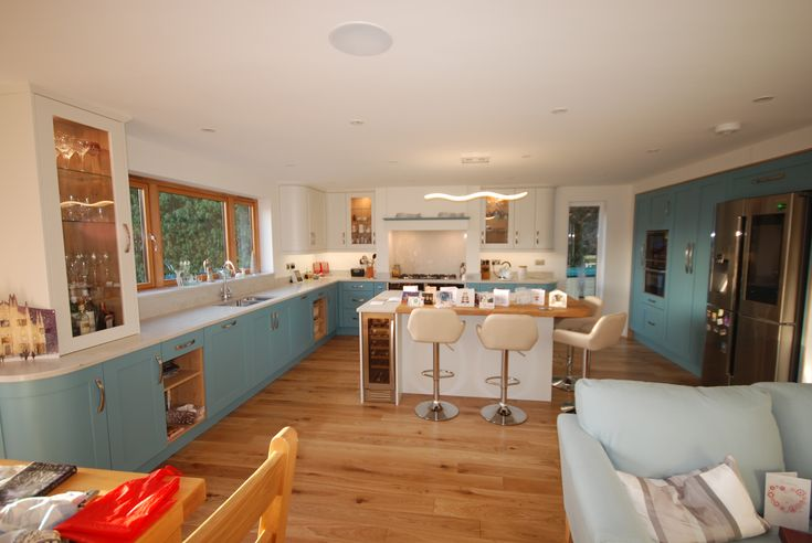 Saffron Interiors Guildford - Taransey smooth painted kitchen in porcelain and stone blue. Fitted with Marbre Carrara quartz and solid oak worktops. Saffron Interiors 01483 511068 #kitchen #design #white #cream #blue #stone #porcelain #quartz #marbre #carrara #island #oak #samsung #neff #canopy #curved