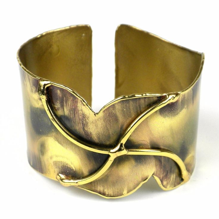 Handcrafted by South African artisans, this darkened brass cuff features a pinwheel design in polished brass. The feathering and color on this 1.5-inch bracelet is achieved by applying extreme heat rather than paints or dyes.