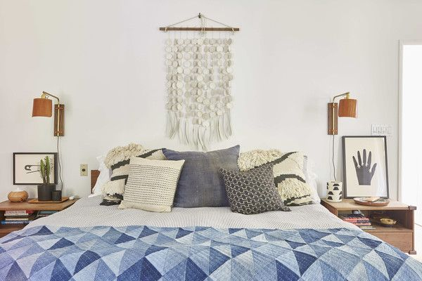 Modern bohemian bedroom design with a white, beige, tan, and blue color palette and a distinctive wall hanging above the bed - Global Decor & Boho Decorating Ideas