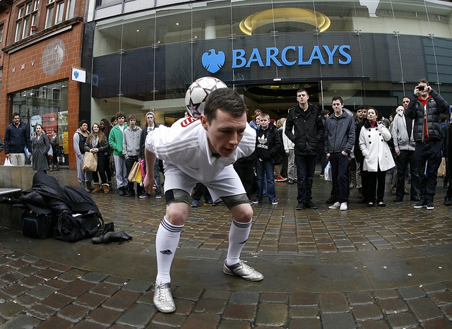 A football freestyler performs outside a Barclays branch, via Flickr.