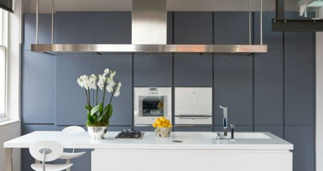 The sleek kitchen, featuring the Corian island unit and full width extractor hood