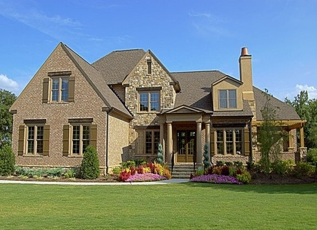 Four columns flank the double-door entry to this brick and stone home accented by rustic shutters. By John Wieland Homes. The Woodmont Golf and Country Club. Canton, GA. #StartFreshBuyNew