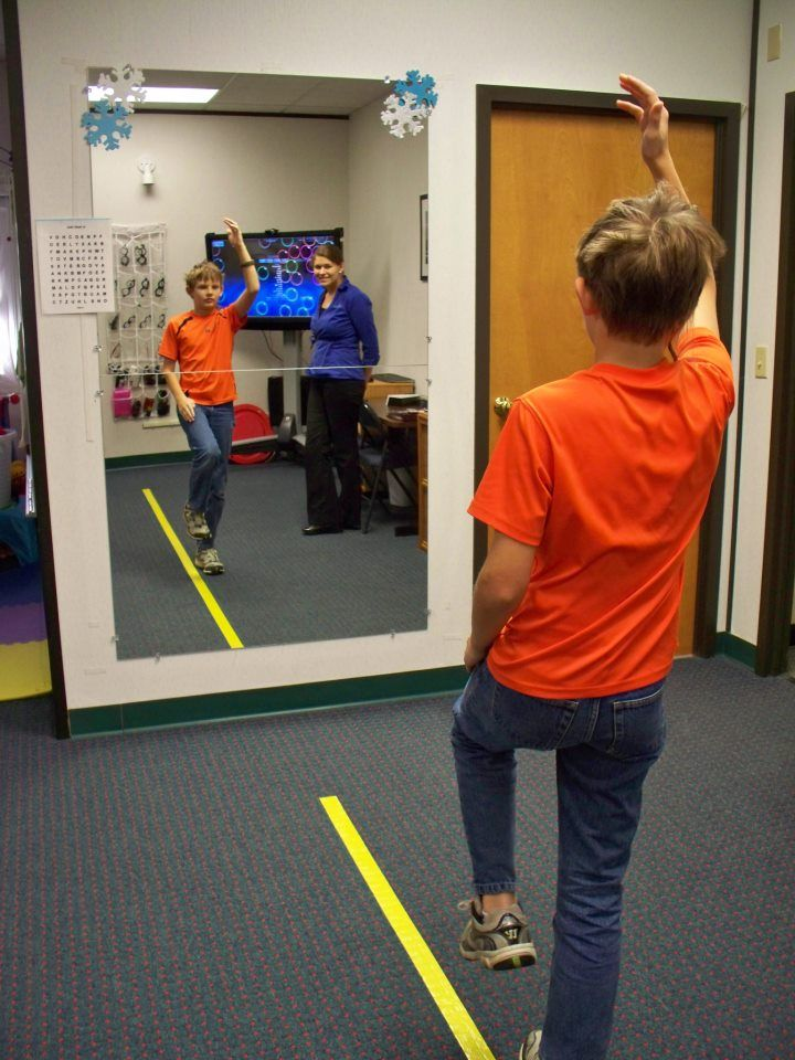 Helping a patient to develop bilateral integration is a core component to a child's vision development. In this example, Krystal is doing an activity with Alex that works on reciprocal interweaving on his midline while incorporating balance. By using the full length mirror in this technique Alex has better awareness and feedback.