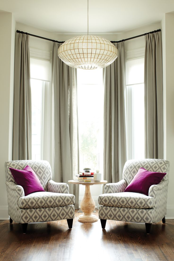 How to make the room look bigger: Living room, two armchairs, large chandelier, tall windows, drapes hung really high.