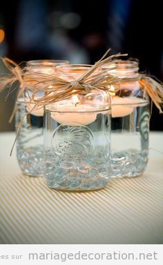 DIY candles floating in jars with clear marbles in bottom with raffia bows around top