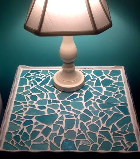 An old table was made over with a sea glass mosaic. The table top was spray-painted white first, then sea glass pieces were adhered with clear glass adhesive, finished off with pre-mixed grout. By Lisa of Uppercase Living, via Pinterest.