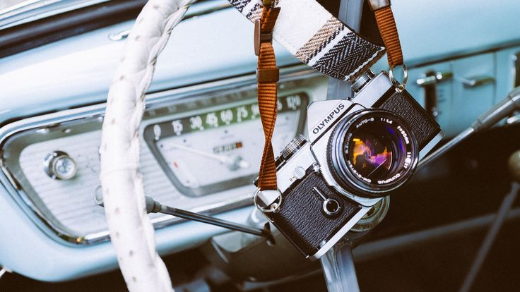 Olympus camera and strap on top of a white steering wheel in a vintage car - free high resolution images by Nick Schreger | UNSPLASH.COM #vintagecameras