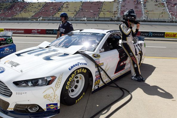 Brad Keselowski, driver of the #2 Miller Lite Ford, adjusts his helmet on the grid during qualifying for the NASCAR Sprint Cup Series Quicken Loans 400 at Michigan International Speedway on June 13, 2014 in Brooklyn, Michigan.