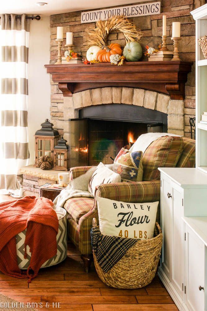Stone fireplace in family room with fall decor and lanterns