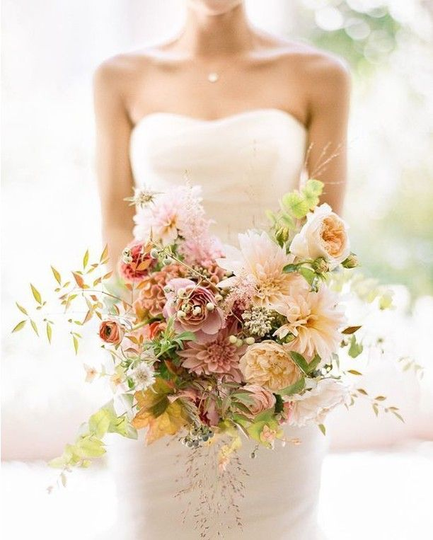 ith the perfect warm color palette for a late summer wedding, @saipua combined dahlias, garden roses, celosia, and ranunculus with foraged foliages. Photo by @heatherwaraksa.  #weddingflowers #weddingbouquet #bridalbouquet