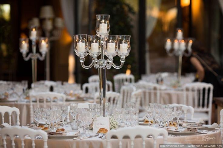 Mise en place minimal con candelabri per un matrimonio elegante. Tavoli rotondi e composizioni essenziali.